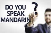 Business man pointing to transparent board with text: Do you Speak Mandarin?