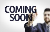 Business man pointing to transparent board with text: Coming Soon