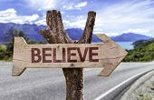 Believe wooden sign with landscape background
