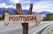 Positivism wooden sign with landscape background