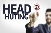 Business man pointing to transparent board with text: Head Hunting