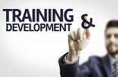 Business man pointing to transparent board with text: Training & Development