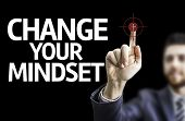 Business man pointing to black board with text: Change Your Mindset