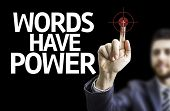 Business man pointing to black board with text: Words Have Power