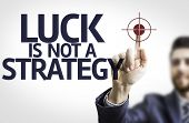 Business man pointing to transparent board with text: Luck is Not a Strategy