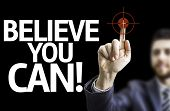 Business man pointing to black board with text: Believe you Can!