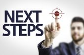 Business man pointing to transparent board with text: Next Steps