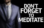 Don't Forget to Meditate written on a board with a business man on background