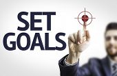 Business man pointing to transparent board with text: Set Goals