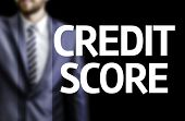 Credit Score written on a board with a business man on background