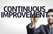 Business man pointing to transparent board with text: Continuous Improvement
