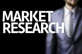 Market Research written on a board with a business man on background