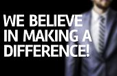 We Believe in Making a Difference written on a board with a business man on background
