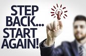 Business man pointing to transparent board with text: Step Back Start Again