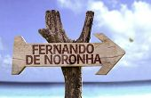 Fernando de Noronha wooden sign with a beach on background