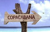 Copacabana wooden sign with a beach on background