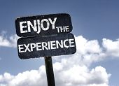 Enjoy The Experience sign with clouds and sky background