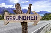 Health (In German) wooden sign with a road background
