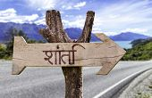 Peace (In Hindi) wooden sign with a road background