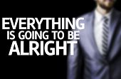 Everything is going to be Alright written on a board with a business man on background
