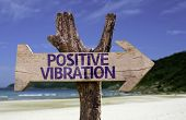 Positive Vibration wooden sign with a beach on background