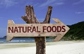 Natural Foods wooden sign with a beach on background
