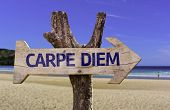 Carpe Diem wooden sign with a beach on background