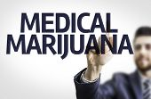 Business man pointing to transparent board with text: Medical Marijuana