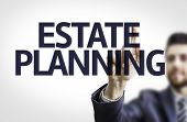 Business man pointing to transparent board with text: Estate Planning