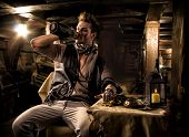 stock photo of buccaneer  - Handsome Rugged Male Pirate Drinking from Bottle in Ship Quarters - JPG