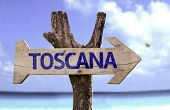 Tuscany (In Italian) wooden sign with a beach on background