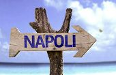 Naples (In Italian) wooden sign with a beach on background