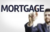 Business man pointing to transparent board with text: Mortgage
