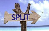 Split wooden sign with a beach on background