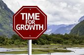 Time For Growth written on red road sign with landscape background