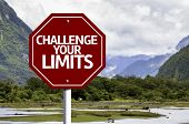 Challenge your Limits written on red road sign with landscape background