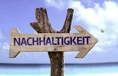 Sustainability (In German) wooden sign with a beach on background