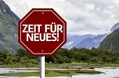 Time For New (In German) written on red road sign with landscape background