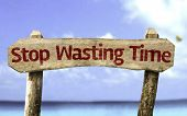 Stop Wasting Time wooden sign with a beach on background
