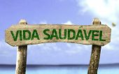 Healthy Life (In Portuguese) wooden sign with a beach on background
