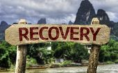 Recovery wooden sign with a forest background