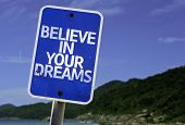 Believe in Your Dreams sign with a beach on background