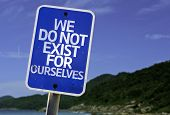 We Do Not Exist for Ourselves sign with a beach on background