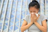 stock photo of sneezing  - young asian woman sneeze her nose outdoor - JPG