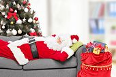 picture of sleeping bag  - Santa Claus sleeping by a Christmas tree on a sofa at home with a bag of presents beside him  - JPG