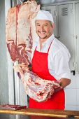 Portrait of happy mature male butcher carrying meat at counter in butchery