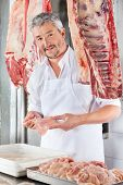 Portrait of confident mature butcher holding chicken meat at counter in shop