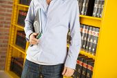 Midsection of young male student holding books while standing against shelf in college library