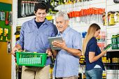 Father and son using digital tablet in hardware store with female customer in background