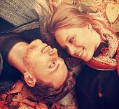 foto of heterosexual couple  - Smiling loving couple lying on autumn leaves in the park top view. Couple in love looking at each other close-up